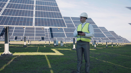 Single caucasian male technician or manager in reflective vest using tablet near large solar power arrays outside