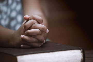 Little girl hands folded in prayer on a Holy Bible in church  for faith concept in vintage color tone