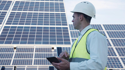 Single handsome male technician or manager in reflective vest and hard hat using digital tablet near large solar power arrays outside