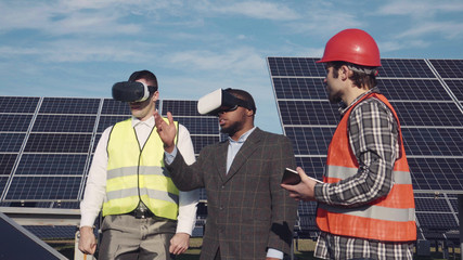 Workman and investor wear virtual reality glasses as they stand near array of solar panels