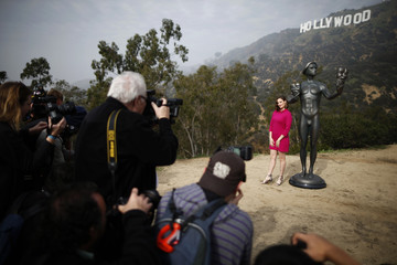 Media members photograph actress Julie Lake standing next to a Screen Actors Guild statue in front of the Hollywood sign in Los Angeles