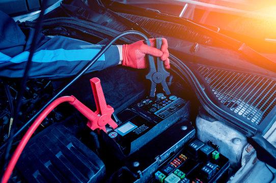Accumulator charging. Hands and terminals. Car repair.