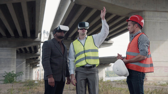 4K shot of business team of two architects and afro american foreman in suit uses virtual reality glasses to discuss a project of development while standing under overpass construction.
