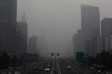 Vehicles run on Jianguo Road on a hazy day in Beijing's central business district