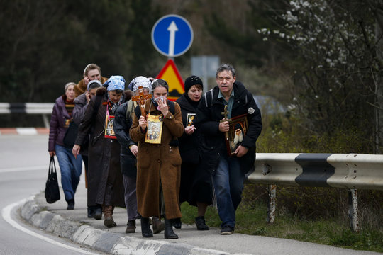 Group of Orthodox Christians carry crosses and icons as they walk along a street in Yalta