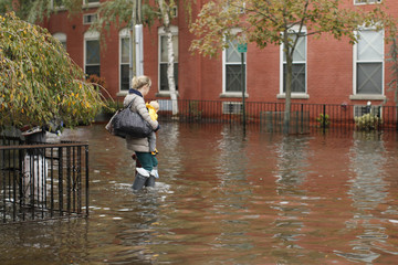 A woman carries her baby as she makes her way out of the floodwaters in Hoboken