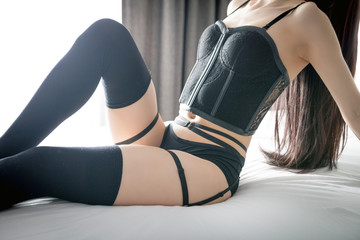 Young woman in erotic lingerie posing on bed at home
