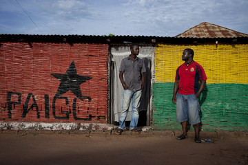 Men stand outside a cafe painted in the logo of Guinea-Bissau's most powerful political party, PAIGC, in the capital Bissau