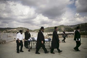 Ultra-Orthodox Jewish men wheel the body of American-Israeli Lakin, during his funeral in Beit Shemesh