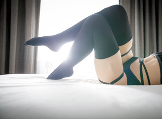 Woman in erotic lingerie and black knee socks posing on bed at home