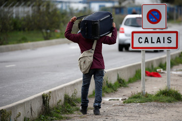 A migrant carries his belongings as they depart the Calais camp called the 'Jungle\