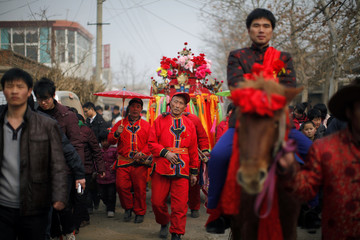 Liu Jian of China rides a horse in front of local residents carrying a sedan chair with his fiance Rebecca Kanthor of the U.S. during their traditional Chinese wedding in Dong'an at the central province of Henan