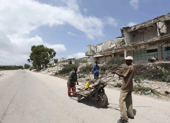 Internally displaced men collect recyclable steel along a war-ravaged street in Somalia's capital Mogadishu