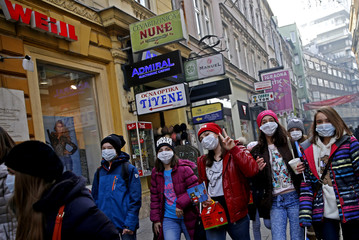 Children walk with protective masks on the street as smog blankets Sarajevo