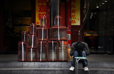 A shop assistant sleeps with his head in his lap next to wooden-framed glass containers at a market in central Beijing