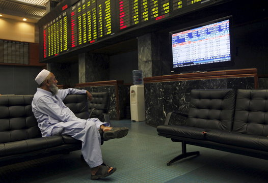 A man sits on couch while monitoring stock prices during a trading session in the halls of Karachi Stock Exchange