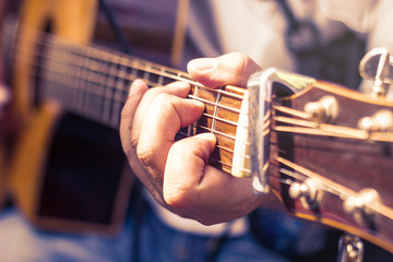 closeup of man's hands playing acoustic guitar, soft vintage style