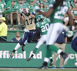 Winnipeg Blue Bombers slotback Nick Moore catches the ball while getting hassled by Saskatchewan Roughriders corner back Terrell Maze in their Classic Labour Day CFL football game in Regina