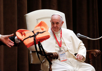 Pope Francis holds a life vest as he meets with youths at the Vatican