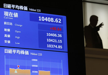 A man is seen next to an electronic board showing the Nikkei stock average before a ceremony marking the end of trading in 2012, at the Tokyo Stock Exchange in Tokyo