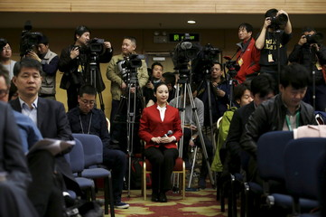 An attendant holding a microphone severs at a news conference by China's Environmental Protection Minister Chen Jining on the sidelines of the National People's Congress (NPC) in Beijing, China