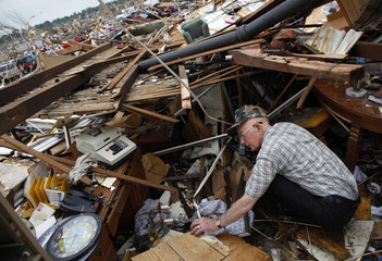 Clovis Steele digs through debris looking for his wallet in his destroyed home after a devastating tornado hit Joplin, Missouri