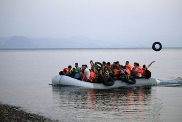 Syrian refugees onboard an overcrowded dinghy approach a beach on the Greek island of Kos