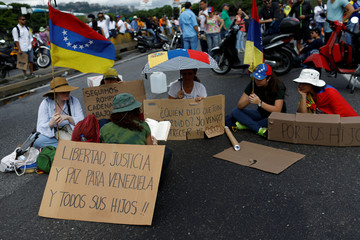 """Opposition supporters waving a national flag, sit on a highway next to placards that read """"Freedom, justice and peace for Venezuela and all its children"""", during a protest against Venezuelan President Nicolas Maduro's government in Caracas"""