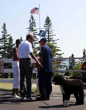 """U.S. President Obama introduces """"Bo"""" his dog to U.S. Coast Guard Commander Chase at Bass Harbor Head Lighthouse in Bass Harbor"""