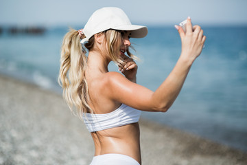 Fitness selfie woman self portrait after workout. Sport athlete is taking selfie photos after working out running and training outdoors on the beach
