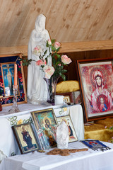 The statue of the virgin Mary on the altar, icons of saints, flowers, oil lamp and candle.