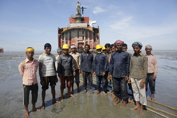 Workers pose for a photograph in front of a wrecked part of a ship at a ship-breaking yard in Chittagong