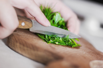 Cutting fresh herbs with a knife on a wooden chopping board. Photos for recipes.