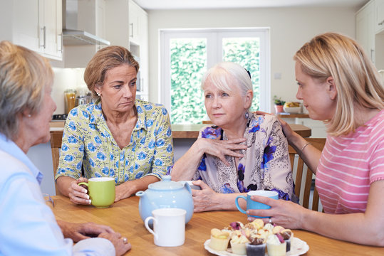 Group Of Women Consoling Unhappy Friend At Home