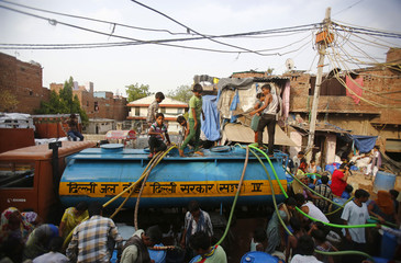 Local residents crowd to collect free drinking water at a slum on a hot summer day in New Delhi