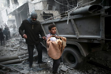 A boy carries a baby in a site hit by what activists said were airstrikes carried out by the Russian air force in the town of Douma, eastern Ghouta in Damascus, Syria