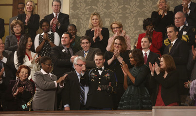 U.S. Army Ranger Sgt. First Class Remsburg gives a thumbs up during a standing ovation for him as President Obama delivers his State of the Union speech in Washington