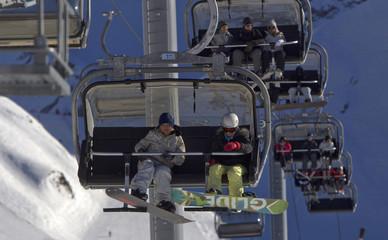 Visitors sit on ski lifts on a slope near the resort of Krasnaya Polyana