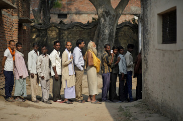 Voters line up to cast their votes at a polling station at Ayodhya