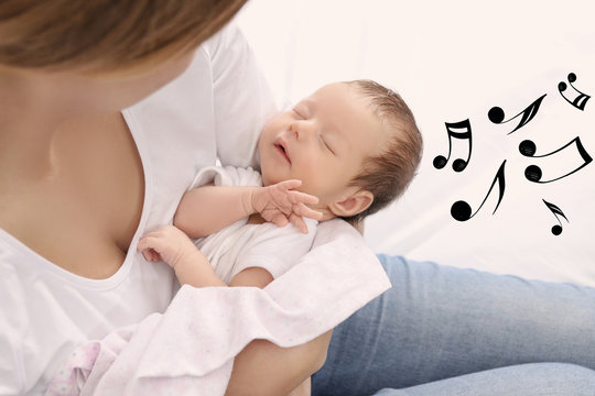 Mother with sleeping baby at home. Lullaby songs and music concept
