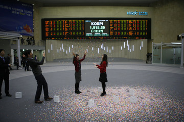 Employees of the Korea Exchange take photographs in front of the final stock price index after the ceremonial closing event of the 2014 stock market, at the Korea Exchange in Seoul