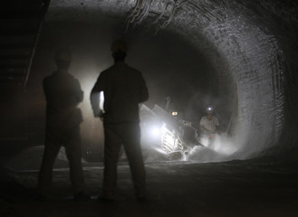 Employees stand near a milling cutter in a pilot mine which is being tested for potential use as a permanent nuclear waste storage facility in Gorleben