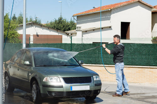 car washing man cleaning car using high pressure water and brush outdoor photo libre de. Black Bedroom Furniture Sets. Home Design Ideas