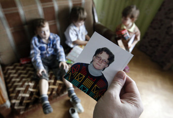 Gorlov, husband of Russian activist Davydova, holds up a photo of her, as their children are seen in the background, at their home in Vyazma