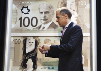 Mark Carney walks past replications of the new Canadian 100 dollar bill made of polymer in Toronto