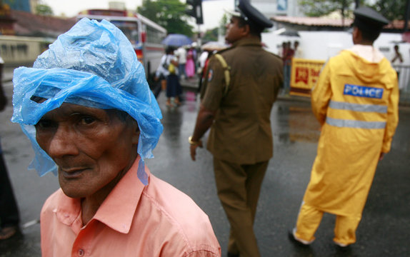 A member of an opposition party listens to speakers in the rain, as police divert traffic in the background, during a protest against the government, and the arrest of General Fonseka in Colombo.