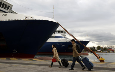 Passengers carry their luggage during a 48-hour seamen strike at the port of Piraeus near Athens