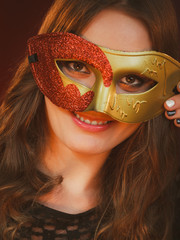 Closeup woman face with carnival golden red mask on dark