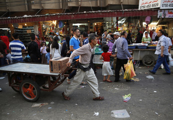 A worker pulls a cart at a market in Arbil