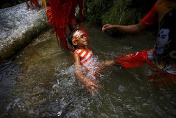"Hindu devotees help a boy take a holy dip on the Bagmati River during the ""Bol Bom"" pilgrimage in Kathmandu"